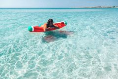 Man on lilo on the beach. Man on lilo in the sea water. Human relaxing on inflatable ring on the beach. Summer vacations Stock Image