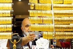 Man lines up gold bracelets Royalty Free Stock Photos