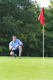Man Lining Golf Shot - vertical. A man kneels, as he tries to line up a shot while golfing. Vertically framed shot Stock Photo