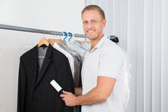 Man with lint roller in clothes store Stock Photos