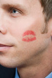Man with lipstick kiss on cheek Stock Image