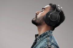 Man listening music on gray background royalty free stock photo