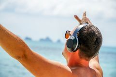 Man Listen Music in Headphones on the Beach. Back View Stock Image