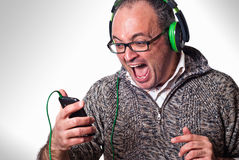 Man listen music on headphones and scream aloud. Music mobile concept Stock Images