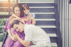 Man is listen pregnant of wife, asian handsome father take care mother and kid with couple and expect maternity have a happy. Love of family concept stock photo