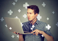 Man listening computer with stethoscope looking at pc laptop. Stock Images