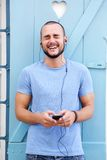 Man listening with earphones on mobile phone and laughing Stock Photos