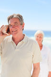 Man listening his shell with his wife behind him Royalty Free Stock Photo