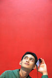 Man listening music. On red copy space stock image