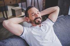 Man listening music in earphones. And relaxing on the sofa at home Stock Photos