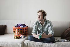 Man Listening Music While Folding Laundry On Sofa Stock Photography