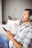 Man listening music while holding mobile phone. Close-up of man listening music while holding mobile phone on sofa at home Royalty Free Stock Photography
