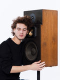 Man listening  music lover speakers. Studio portrait of a one caucasian young man listening to music lover with speakerphones  on white background Stock Image