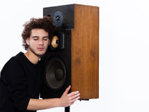 Man listening  music lover speakers. Studio portrait of a one caucasian young man listening to music lover with speakerphones isolated on white background Royalty Free Stock Image