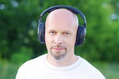 Man listening music outdoors in wireless headset Royalty Free Stock Photos