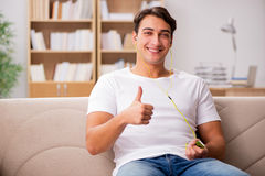 The man listening music sitting in couch. Man listening music sitting in couch Stock Photo