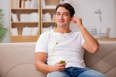 The man listening music sitting in couch. Man listening music sitting in couch Stock Image