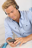 Man listening music with smartphone in office Stock Photos