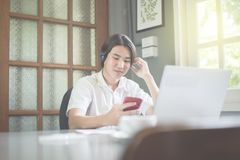 Young man listening music using mobilephone and headphone in coffee shop,feeling relax. Man listening music using mobilephone and headphone in coffee shop Royalty Free Stock Photo