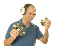 Man listening music vintage head phones. Middle age senior man listening to music cd discs with vintage head phones and holding discs Royalty Free Stock Photos
