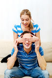 Man listening music, woman covering his eyes Stock Photos