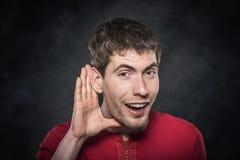 Man listening something over dark background. Royalty Free Stock Images