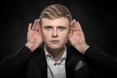 Man listening something over dark background. Stock Image