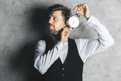 Man listening to alarm clock. Businessman listening to silver alarm clock mechanism on concrete background with shadow Stock Photos