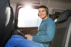 Man listening to audiobook through headphones. In car Royalty Free Stock Images