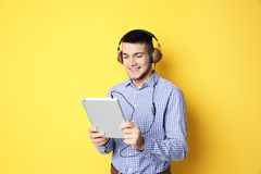 Man listening to audiobook through headphones. On color background Royalty Free Stock Photography