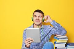 Man listening to audiobook through headphones. On color background Royalty Free Stock Images