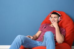 Man listening to audiobook through headphones. Near color wall Stock Photography