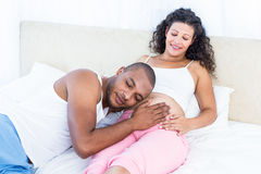 Man listening to belly of happy pregnant wife on bed Stock Images