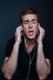 Man is listening to favourite music with back v-neck. Shirt on dark background Royalty Free Stock Images