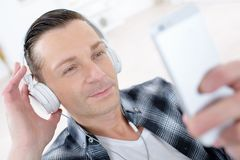 Man listening to headphone connected on cellular phone Stock Photos