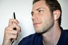 Man listening to his ipod. A young man while listening musis on his ipod Royalty Free Stock Photo