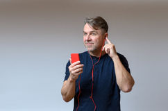 Man listening to his mobile through earplugs. Man listening to colorful bright red his mobile through earplugs with a smile of pleasure as he enjoys the music or Royalty Free Stock Images