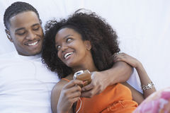 Man Listening To MP3 Player And Hugging Girlfriend Royalty Free Stock Photography