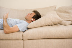 Man listening to mp3 player on sofa, eyes closed, side view Stock Image