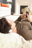 Man Listening To MP3 Player Laying On Rug Stock Photos