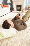 Man Listening To MP3 Relaxing On Rug Royalty Free Stock Image