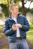 Man Listening To MP3 Whilst Walking In Autumn Park Stock Photography
