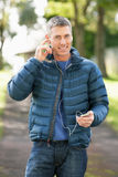 Man Listening To MP3 Whilst Walking In Autumn Park Royalty Free Stock Image