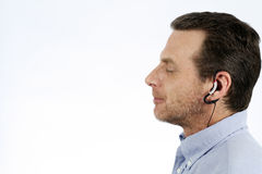 Man Listening to Music. Adult male hearing music on stereo headphones, happy and relaxed with eyes closed Royalty Free Stock Photos