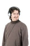 Man listening to music. A young man listening to music on large retro headphones stock image