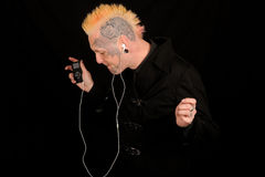 Man listening to music. A man with tattoos listening to music on an MP3 player Stock Images