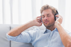 Man listening to music on a couch Royalty Free Stock Images