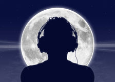 Man listening to the music at the full moon. Silhouette of a man in headphones listening to the music with the full moon on the background Royalty Free Stock Photo