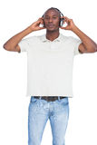 Man listening to music with hands on his headphones Royalty Free Stock Photos