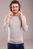 Man listening to music. Happy young man with headphones on and listening to music Stock Photo